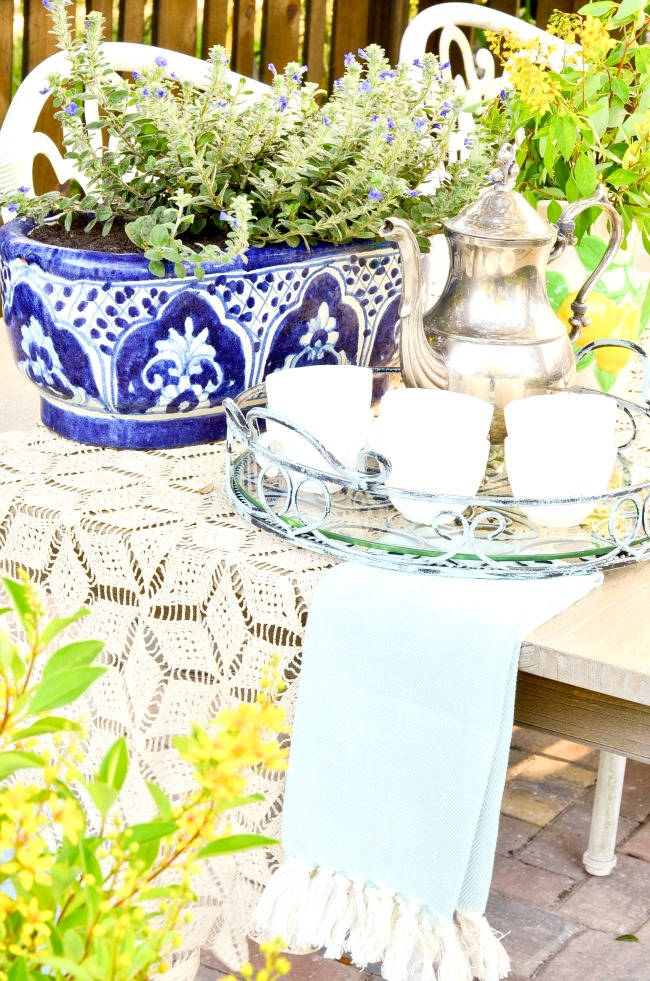 Layering elements like a crochet table runner and a Turkish towel add textile interest to this table setting using a tray.